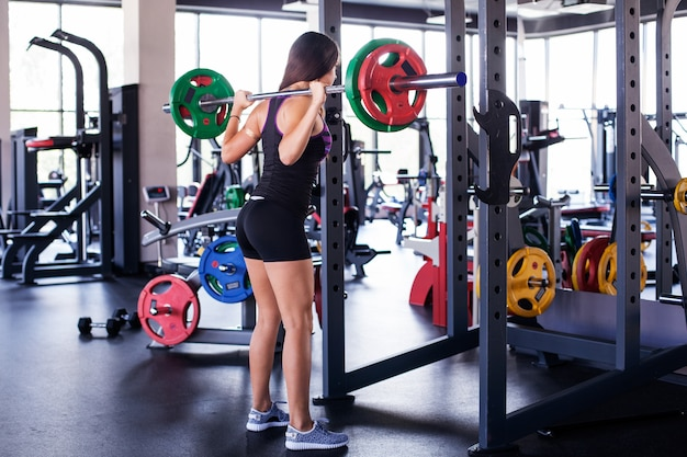 Giovane donna atletica che tiene un bilanciere sulle spalle in palestra