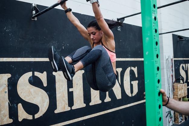 Giovane donna atletica facendo pull up alla barra di ginnastica aiutato da personal trainer