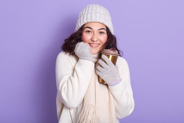 Giovane donna attarctive che prende il sole le sue mani tramite la tazza della bevanda calda e dei guanti