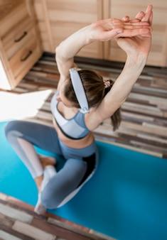 Giovane donna attiva che allunga sulla stuoia di yoga