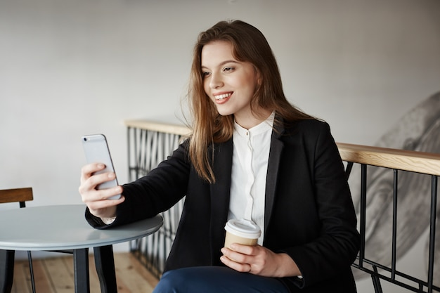 Giovane donna attraente al caffè con lo smartphone