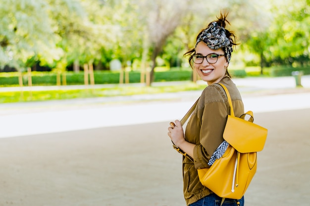 Giovane donna attraente allegra con lo zaino giallo