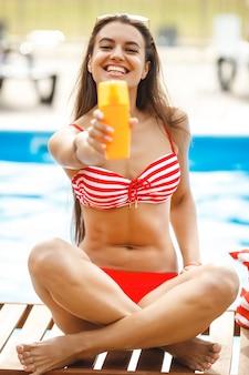 Giovane donna attraente che applica la crema della protezione solare
