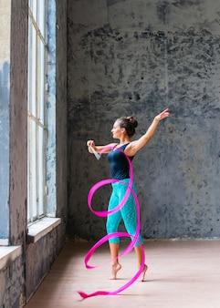 Giovane donna attraente che balla con il nastro rosa