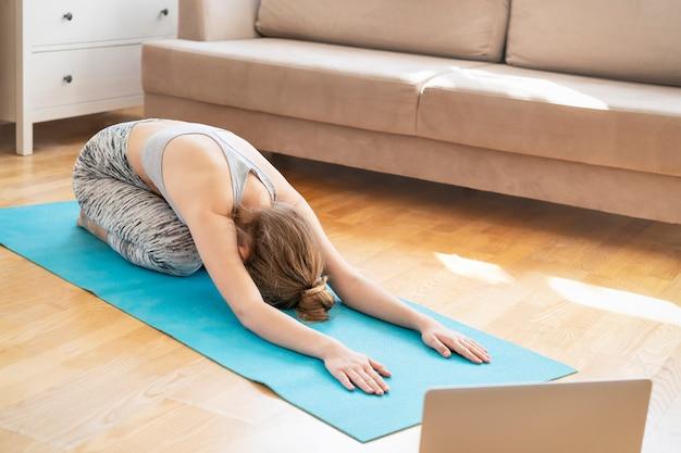 Giovane donna attraente che fa esercizio di yoga a casa, balasana, posa del bambino, mezza posa della tartaruga di ardha-kurmasana in salone. allenarsi indossando reggiseno e pantaloni sportivi. concetto di assistenza sanitaria