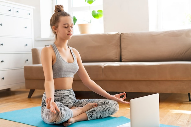 Giovane donna attraente che fa esercizio di yoga a casa yoga a casa nella posizione del loto, esercizio di ardha padmasana, mezza posa di loto in salotto. allenarsi indossando reggiseno e pantaloni sportivi. assistenza sanitaria