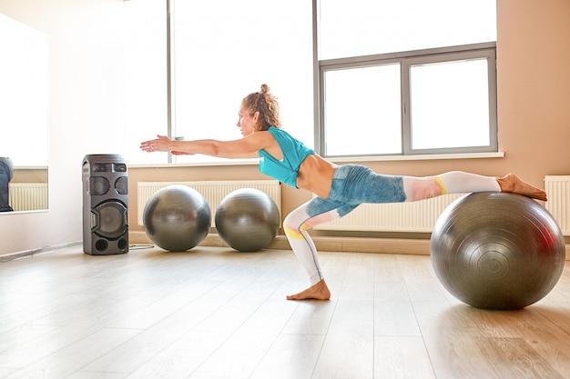 Giovane donna attraente che fa yoga nella stanza di forma fisica.