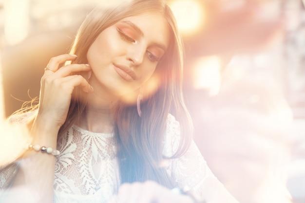 Giovane donna attraente che fantastica e che guarda attraverso la finestra