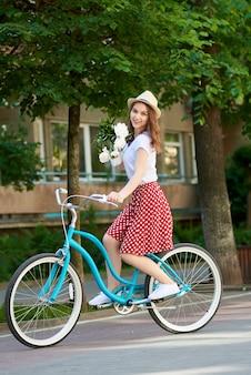 Giovane donna attraente che gode guidando la sua bicicletta