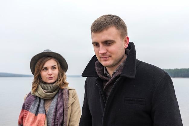 Giovane donna attraente che guarda il suo ragazzo un giorno di inverno nebbioso freddo