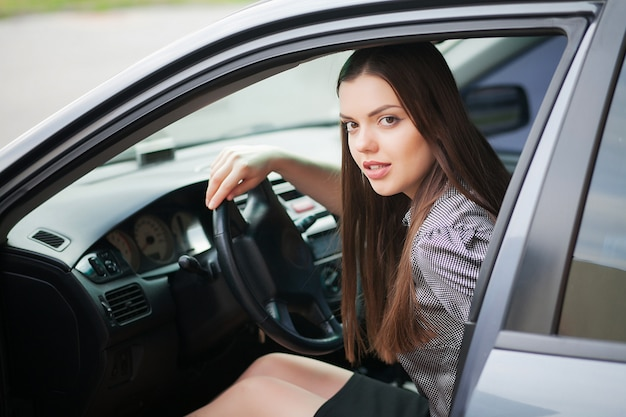 Giovane, donna attraente che guida un'auto