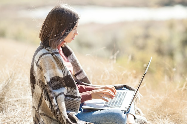 Giovane donna attraente che lavora al computer portatile all'aperto. donna che fa il suo lavoro indipendente sul pc. lavoratore a distanza in vacanza.