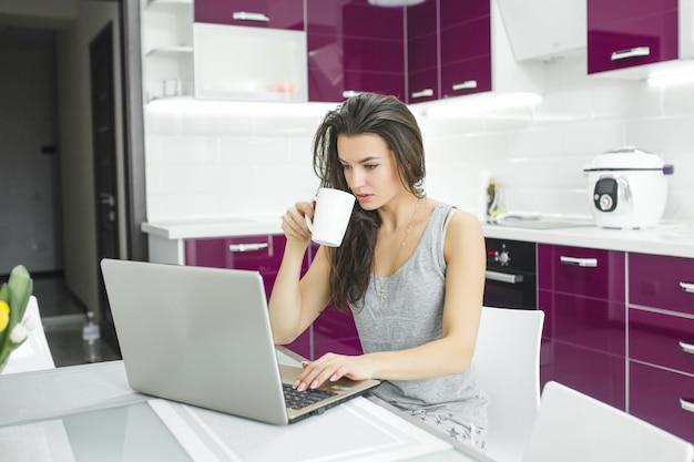 Giovane donna attraente che lavora al pc in cucina. lavoro femminile al computer di mattina. libero professionista al computer portatile al coperto.