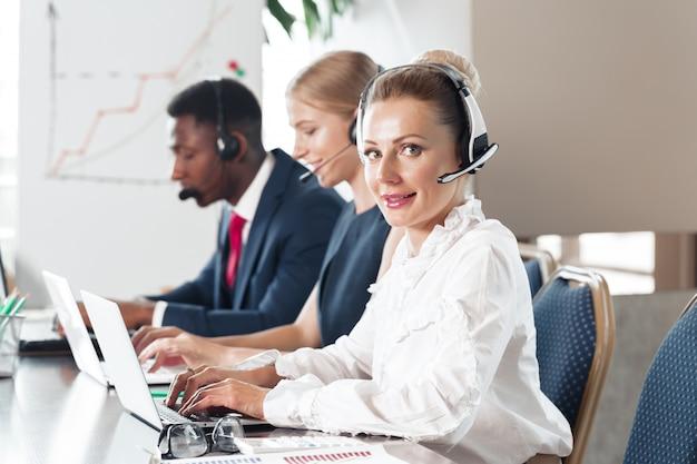 Giovane donna attraente che lavora in un call center con i suoi colleghi