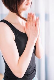 Giovane donna attraente che medita a casa