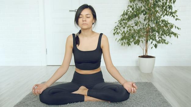 Giovane donna attraente che medita con gli occhi chiusi mentre sedendosi sul pavimento a casa. rilassamento e yoga durante l'autoisolamento