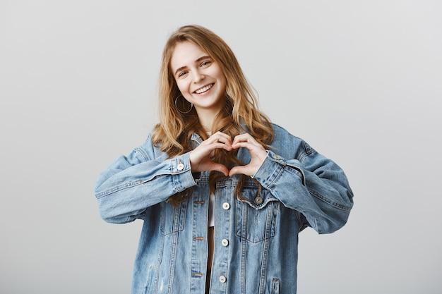 Giovane donna attraente che mostra il gesto del cuore per esprimere come, simpatia o amore