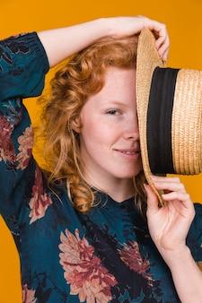 Giovane donna attraente che nasconde la metà del viso con cappello