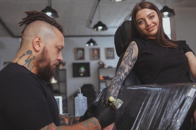 Giovane donna attraente che ottiene nuovo tatuaggio dal tatuatore professionista