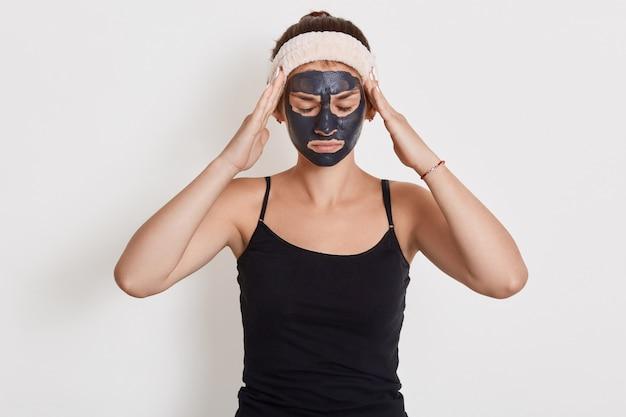 Giovane donna attraente che posa con gli occhi chiusi e che tiene le mani sulle tempie, che soffre dal dolore, che indossa la fascia per capelli e la maglietta senza maniche, facendo le procedure cosmetiche a casa, posando con la maschera di fango.