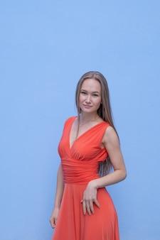 Giovane donna attraente che posa con il vestito rosso in parete blu