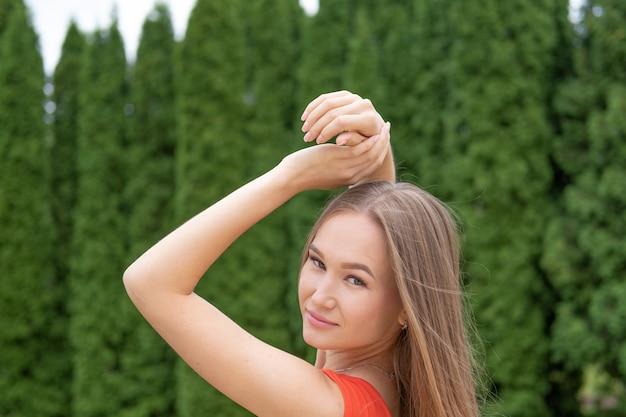 Giovane donna attraente che posa con il vestito rosso nel parco