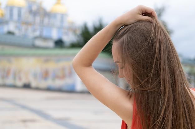 Giovane donna attraente che posa con il vestito rosso nella via, vista posteriore