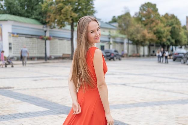 Giovane donna attraente che posa con il vestito rosso nella via