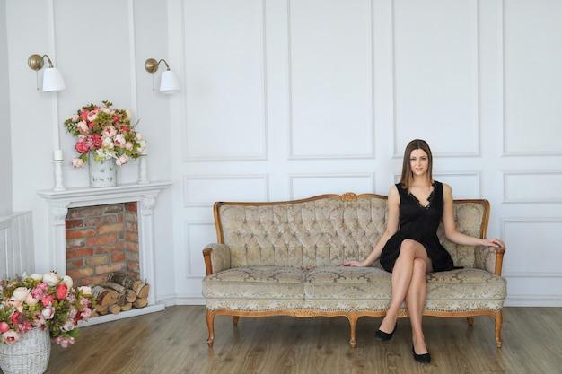 Giovane donna attraente che posa in sofà
