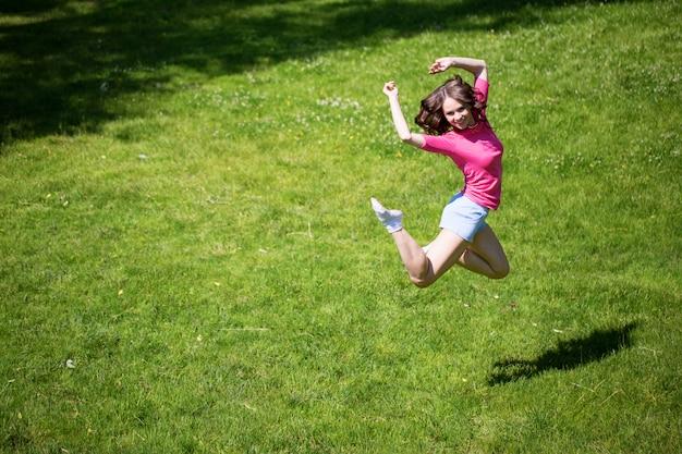 Giovane donna attraente che salta nel parco estivo