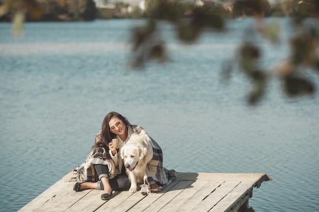 Giovane donna attraente che si siede al molo con il suo cane. migliori amiche all'aperto