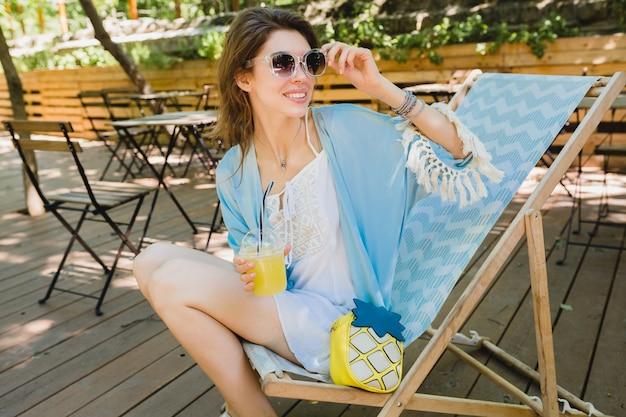 Giovane donna attraente che si siede nella sedia a sdraio in abito di moda estiva, abito bianco, mantello blu, occhiali da sole, sorridente, bere limonata, accessori alla moda, relax in vacanza