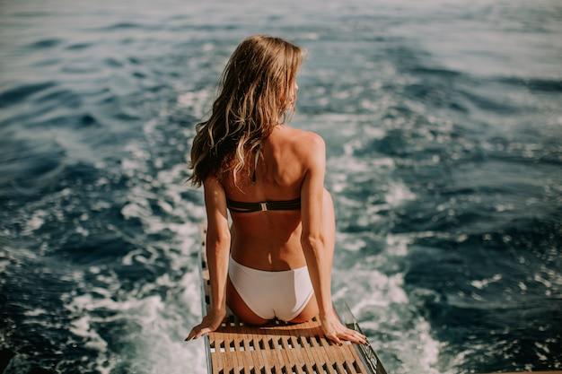 Giovane donna attraente che si siede sull'yacht di lusso che galleggia in mare
