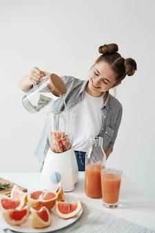 Giovane donna attraente che sorride aggiungendo acqua in miscelatore con i pezzi ed i rosmarini di pompelmo. nutrizione alimentare dieta sana.