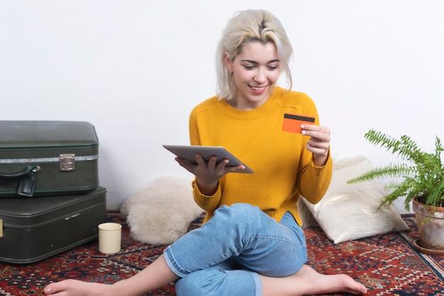 Giovane donna attraente che usando la sua carta di credito per effettuare un acquisto online con un tablet touchscreen digitale a casa.