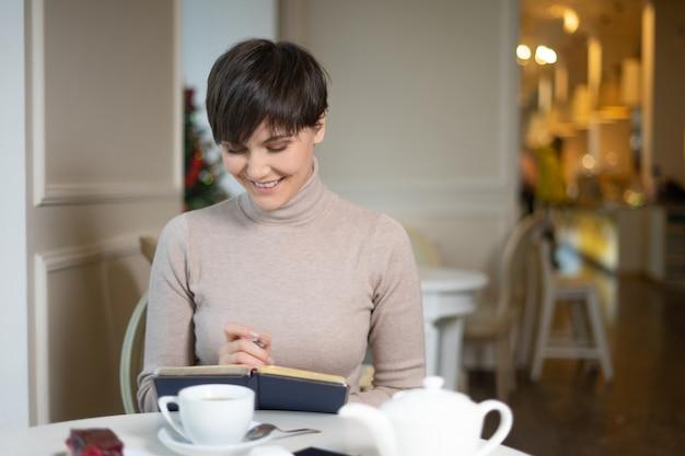 Giovane donna attraente con la penna a disposizione che pensa sui piani e che scrive lista da fare in blocco note che gode del tempo di ricreazione in caffè alla moda