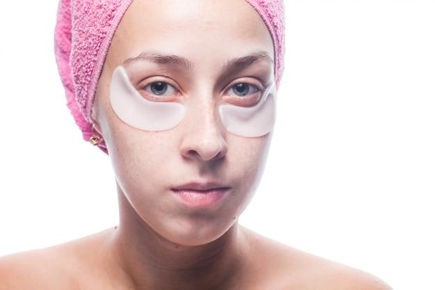 Giovane donna attraente con le toppe bianche sotto gli occhi e un asciugamano rosa sulla sua testa isolata sopra. ritratto del primo piano cura della pelle
