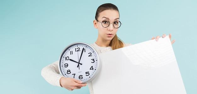 Giovane donna attraente con lo spazio in bianco e l'orologio