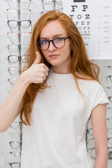 Giovane donna attraente con lo spettacolo che mostra pollice sul gesto che esamina macchina fotografica nel negozio di ottica