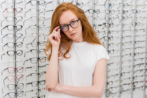 Giovane donna attraente con lo spettacolo nel negozio di ottica