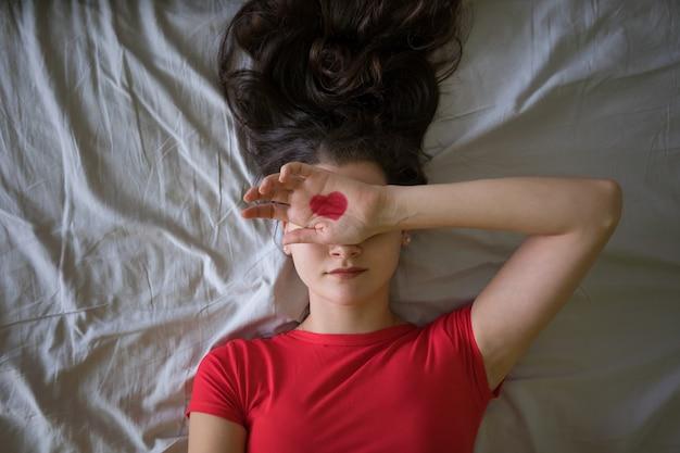 Giovane donna attraente del brunette con il cuore del disegno sulle mani nel letto