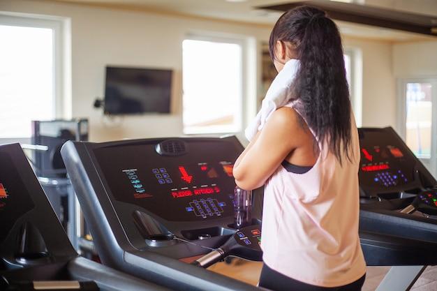 Giovane donna attraente di forma fisica che funziona sulla pedana mobile, indossando in abiti sportivi bianchi, donna sportiva in buona salute che fa esercizio cardio sulla pedana mobile