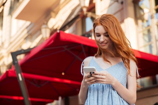 Giovane donna attraente di redhead che per mezzo del telefono mobile