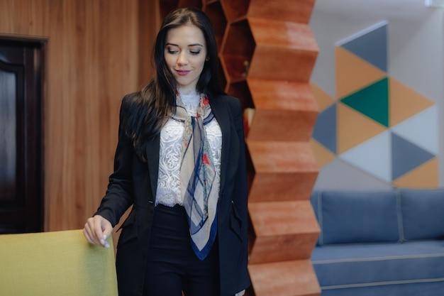 Giovane donna attraente emotiva in uno stile aziendale presso una sedia in un ufficio moderno