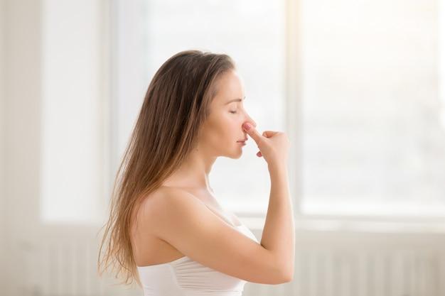 Giovane donna attraente fare alternate nostril respirazione, bianco