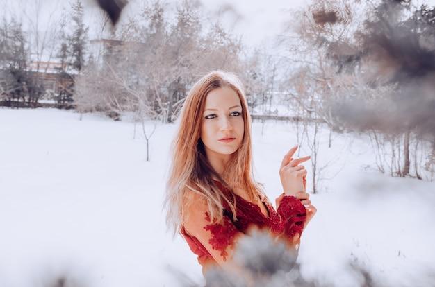 Giovane donna attraente felice che posa in vestito rosso