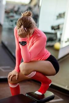 Giovane donna attraente in abiti sportivi che riposa dopo un allenamento su una panchina