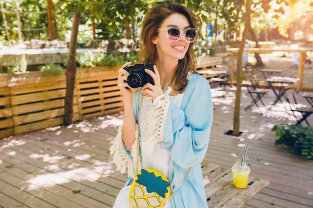 Giovane donna attraente in abito di moda estiva, abito bianco, mantello blu, borsa gialla, occhiali da sole, sorridente, con macchina fotografica d'epoca, accessori alla moda, abbigliamento alla moda