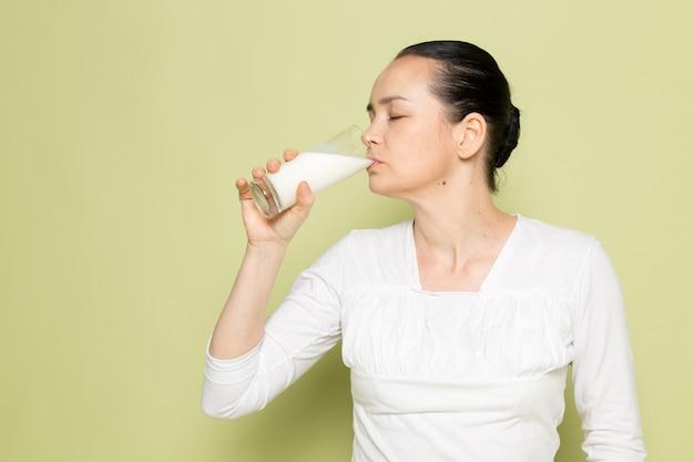 Giovane donna attraente in bicchiere bianco camicia con latte