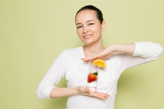 Giovane donna attraente in camicia bianca che giudica di vetro con latte e frutti